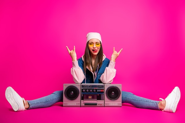 Imagem de corpo inteiro dela, ela é bonita, atraente e alegre, sentada ao lado da caixa de som, mostrando sinais de chifre piscando e piscando isolado em um brilho vívido brilhante rosa vibrante