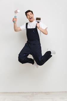 Imagem de corpo inteiro do construtor masculino gritando pulando com o rolo de tinta e o pincel sobre uma parede cinza