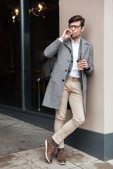Imagem de corpo inteiro do empresário de óculos e casaco