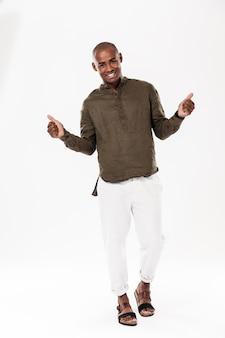 Imagem de corpo inteiro do homem africano sorridente, mostrando os polegares e olhando
