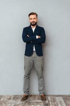 Imagem de corpo inteiro do homem barbudo sorridente em roupas de negócios posando com braços cruzados e olhando para a câmera sobre cinza