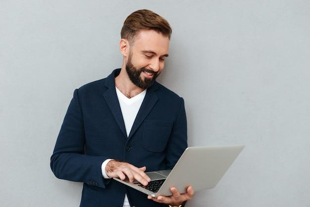 Imagem de corpo inteiro do homem barbudo sorridente em roupas de negócios usando o computador portátil sobre cinza