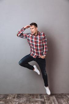 Imagem de corpo inteiro do homem de camisa e calça jeans pulando e olhando de lado