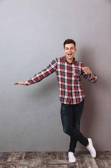 Imagem de corpo inteiro do homem sorridente de camisa e calça jeans tocando copyspace e apontando