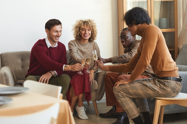 Imagem de corpo inteiro em um grupo multiétnico de adultos contemporâneos tilintando taças de champanhe enquanto desfrutam de um jantar dentro de casa com os amigos