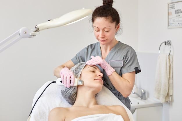 Imagem de cosmetologista morena usa roupas cinza, fazendo procedimentos ultra-sônicos para jovem