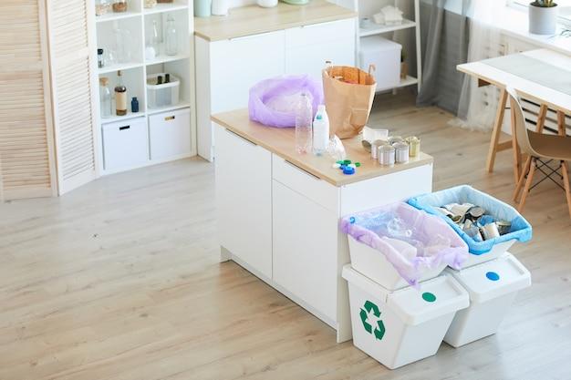 Imagem de cozinha doméstica com lixo na mesa, classificado em sacos de papel ecológico e lixeiras