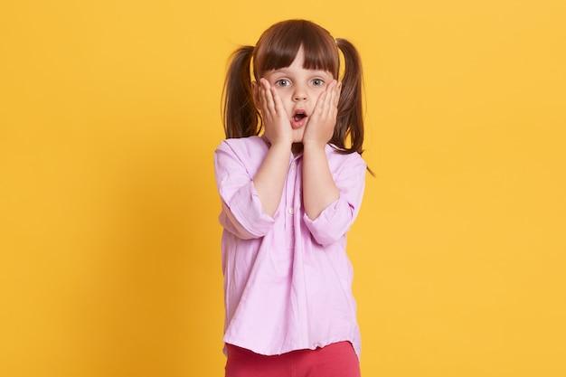 Imagem de criança surpresa assustada emocional, colocando as mãos em cheecks, abrindo a boca e os olhos amplamente, posando isolado sobre parede amarela. conceito de crianças e emoções.