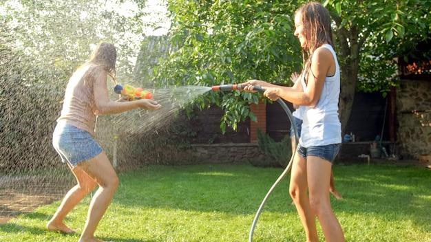 Imagem de crianças alegres felizes wuth jovem mãe brincando com pistolas de água e casa de jardim. família brincando e se divertindo ao ar livre no verão Foto Premium