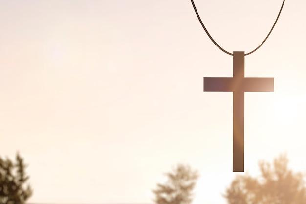 Imagem de cruz cristã com fundo de céu ao pôr do sol