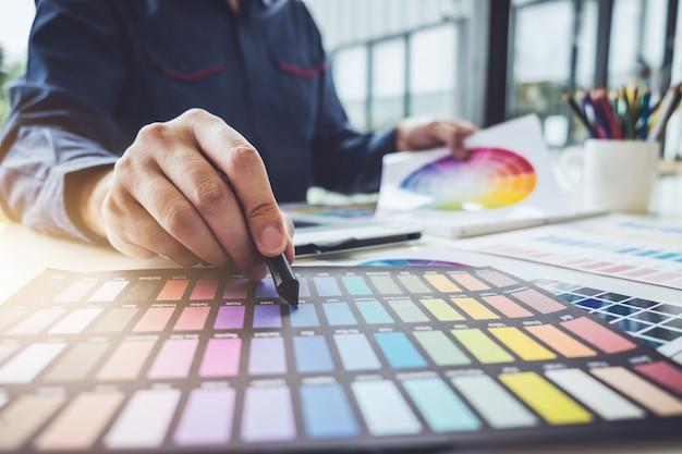 Imagem de designer gráfico criativo trabalhando na seleção de cores e desenho na mesa digitalizadora