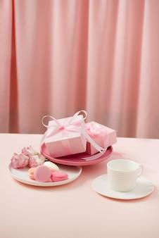 Imagem de dia de mulher / mãe feliz de uma xícara de café ou chá e flor lisianthus com biscoito e presentes ao lado de cortinas de rosa.