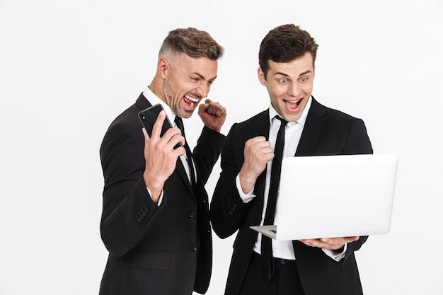 Imagem de dois empresários caucasianos em êxtase em ternos de escritório, gritando enquanto seguram laptop e celulares isolados