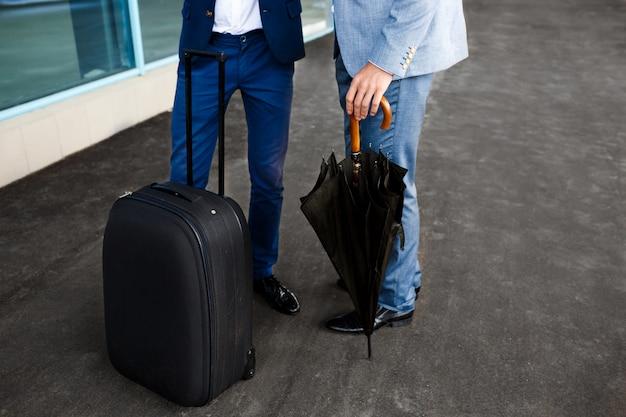 Imagem de dois empresários com guarda-chuva e mala na estação
