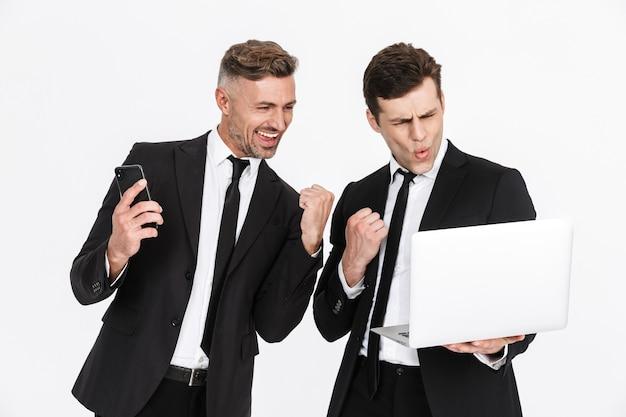 Imagem de dois entusiasmados empresários caucasianos em ternos de escritório, regozijando-se enquanto seguram laptop e celulares isolados