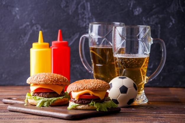 Imagem de dois hambúrgueres, copos, bola de futebol, ketchup