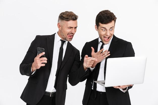 Imagem de dois homens de negócios caucasianos encantados em ternos de escritório, gritando enquanto seguram laptop e celulares isolados