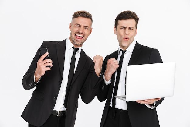Imagem de dois homens de negócios caucasianos felizes em ternos de escritório, regozijando-se enquanto seguram laptop e celulares isolados