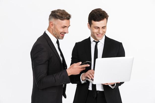 Imagem de dois homens de negócios caucasianos felizes em ternos de escritório segurando laptop e celulares isolados