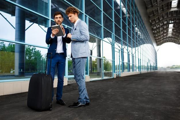 Imagem de dois jovens empresários falando na estação e segurando o tablet