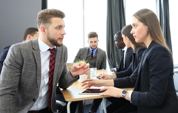 Imagem de dois jovens empresários interagindo em reunião no escritório