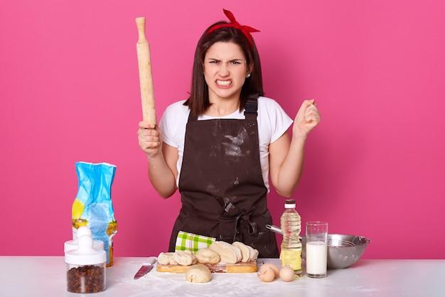 Imagem de dona de casa com raiva irritada, vestindo avental marrom sujo