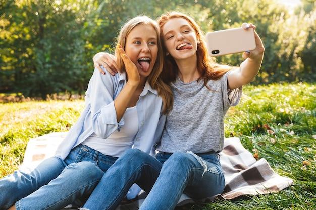 Imagem de duas amigas felizes de jeans, sentadas na grama e tirando uma selfie no smartphone, enquanto descansam no parque de verão