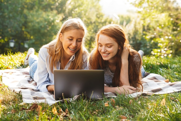 Imagem de duas amigas lindas vestindo roupas casuais, deitadas na grama no parque e usando um laptop prateado