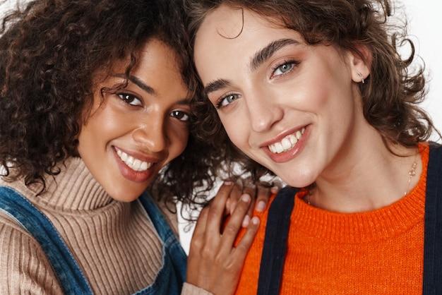 Imagem de duas amigas multirraciais sorrindo muito felizes e sorrindo em macacões jeans