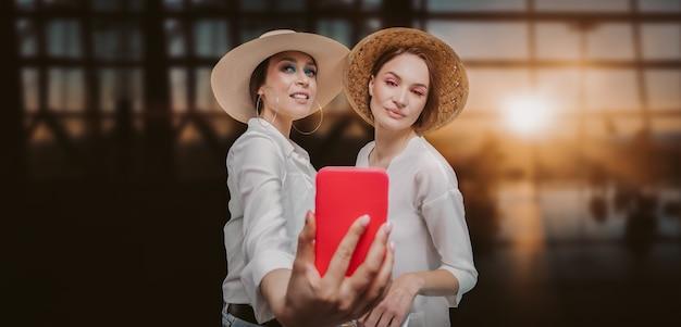 Imagem de duas belas mulheres com chapéus tirando selfies no aeroporto. conceito de viagens. mídia mista