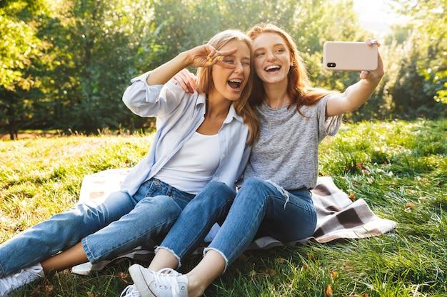 Imagem de duas lindas meninas usando jeans, sentadas na grama no parque de verão e tirando selfie no celular