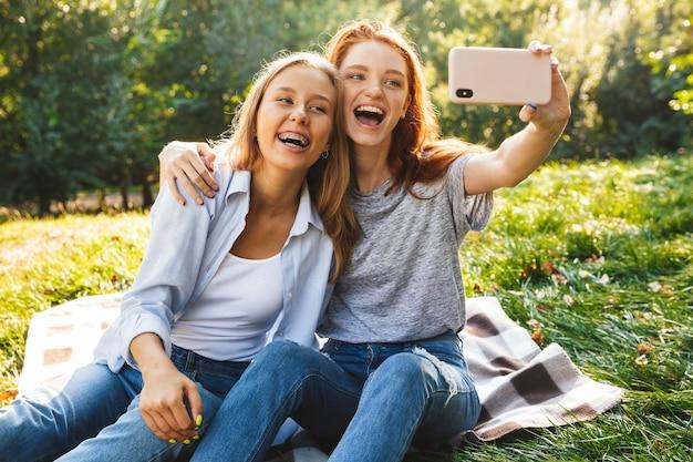 Imagem de duas mulheres alegres, vestindo roupas casuais, rindo, enquanto estão sentadas na grama e tirando uma selfie no celular, enquanto descansam no parque de verão