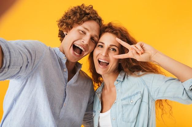 Imagem de duas pessoas caucasianos, um homem e uma mulher, tirando uma foto de selfie e mostrando o símbolo da paz com um sorriso, isolado sobre fundo amarelo