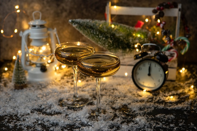 Imagem de duas taças de champanhe na mesa de neve com árvore de natal, lanterna, relógio