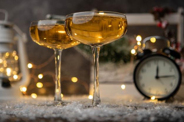 Imagem de duas taças de vinho na mesa com neve, árvore de natal, lanterna, relógio