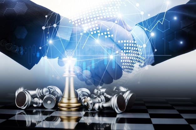 Imagem de dupla exposição do aperto de mão do trabalho da equipe de negócios com gráfico de efeito gráfico e diagrama de conexão de rede com competição de jogo de tabuleiro de xadrez, planejamento, trabalho em equipe e conceito de estratégia de negócios