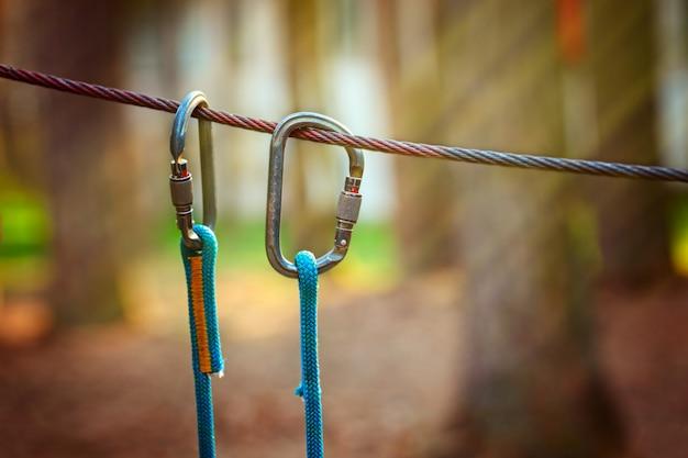 Imagem de esportes de escalada de um mosquetão em uma corda de metal em uma floresta