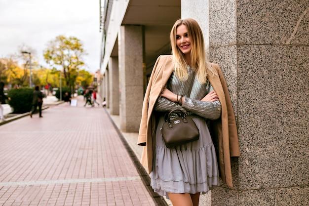 Imagem de estilo de rua de moda de mulher loira elegante, vestindo um vestido de seda de luxo, suéter da moda, casaco de cashmere e bolsa de couro, cores quentes e suaves, clima de primavera, outono, temporada média