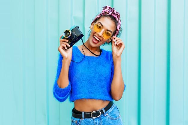 Imagem de estilo de vida ao ar livre da moda mulher negra na camisola de lã brilhante e bandana colorida nos cabelos