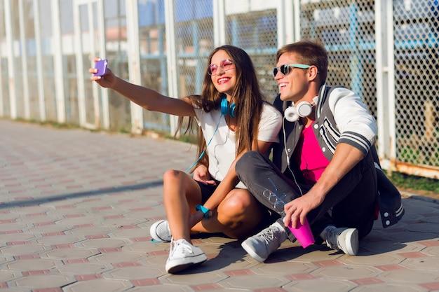 Imagem de estilo de vida de verão de um lindo casal elegante apaixonado fazendo cores de verão auto-retratados.