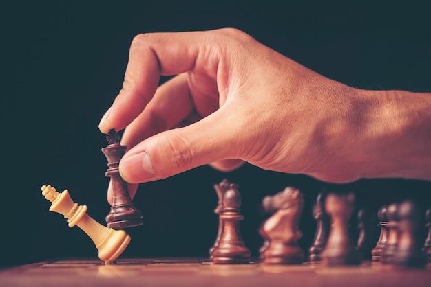 Imagem de estilo vintage de um empresário com as mãos entrelaçadas, planejando a estratégia com xadrez