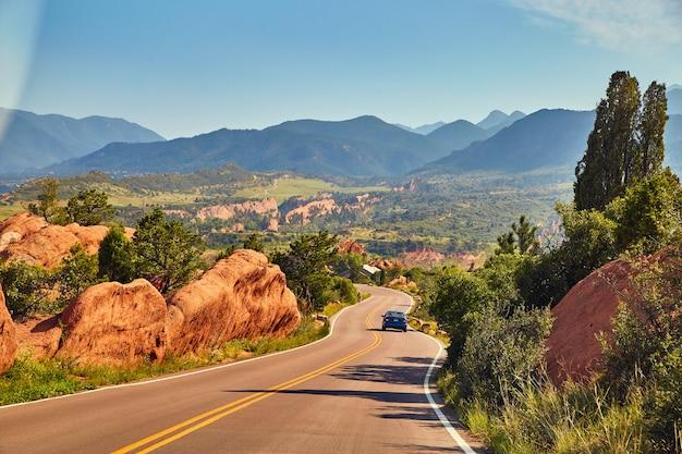 Imagem de estrada aberta com carro passando pela paisagem montanhosa do deserto