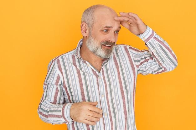 Imagem de estúdio de frustrado e intrigado homem com a barba por fazer sênior, segurando a palma da mão na testa para proteger os olhos do sol, olhando para a poeira ou procurando por algo.