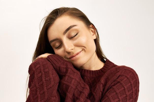 Imagem de estúdio de linda feliz jovem de cabelos escuros, fechando os olhos de prazer, colocando as mãos nas bochechas, vestindo um elegante suéter quente. linda garota curtindo o fio macio no macacão novo, sorrindo