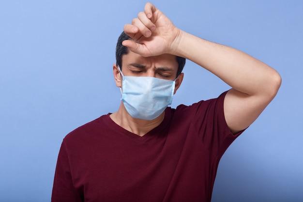 Imagem de estúdio de pobre morena doente com coronavírus, sofrendo de alta temperatura, vestindo máscara antibacteriana e camiseta, fechando os olhos, tendo febre, tendo esgotado a expressão facial.