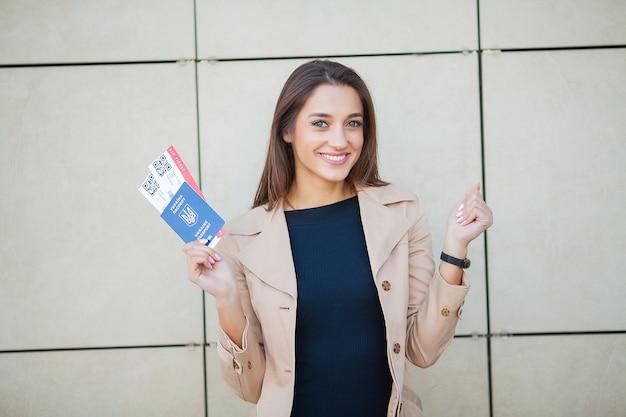 Imagem, de, europeu, mulher, tendo, bonito, cabelo marrom, sorrindo, enquanto, segurando, passaporte, e, ar, bilhetes