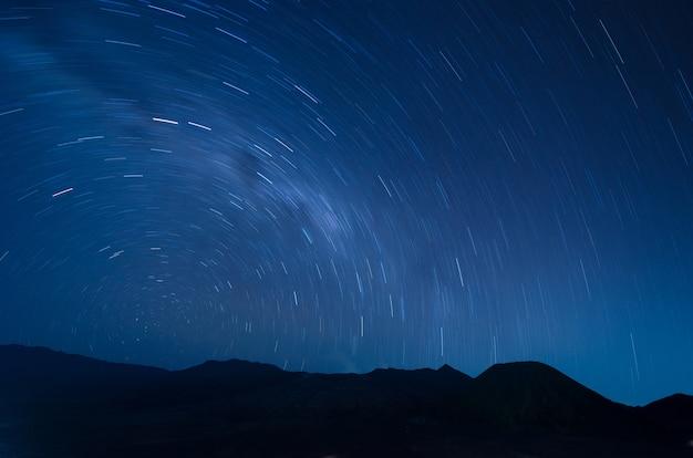 Imagem de extrema longa exposição mostrando fugas estrela acima do vulcão bromo, indonésia
