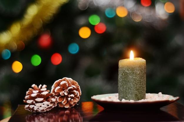 Imagem de fadas de natal com uma vela verde acesa e pinhas no fundo do bokeh de inverno das luzes