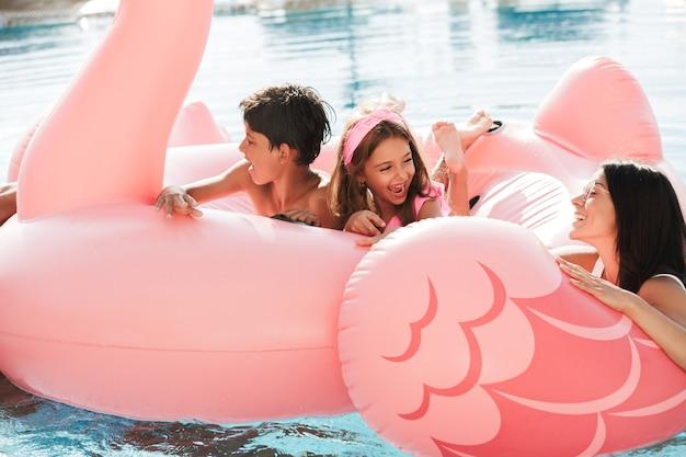Imagem de família animada com duas crianças nadando em uma piscina com anel de borracha rosa, fora do hotel durante as férias