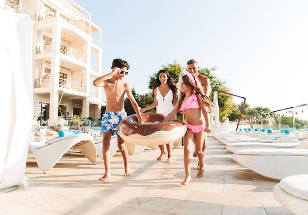 Imagem de família de férias com crianças descansando perto de uma piscina de luxo, com espreguiçadeiras e guarda-sóis brancos na frente do hotel